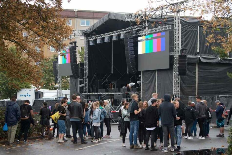 Konzertbesucher warten auf dem Parkplatz an der Johanniskirche hinter einer Absperrung vor der Bühne.