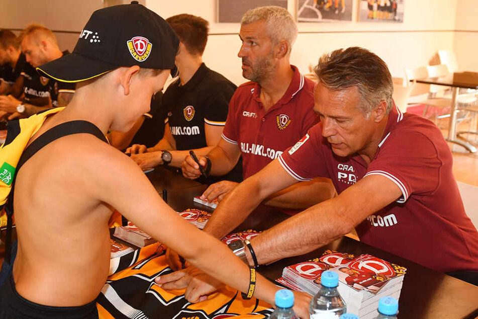 Immer für die Fans da: Uwe Neuhaus (r.) schreibt fleißig Autogramme.