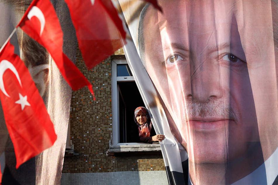 Die Türkei vor den Wahlen: Eine Frau blickt in Istanbul aus ihrem Fenster hinter einem Banner des türkischen Präsidenten Erdogan hervor.
