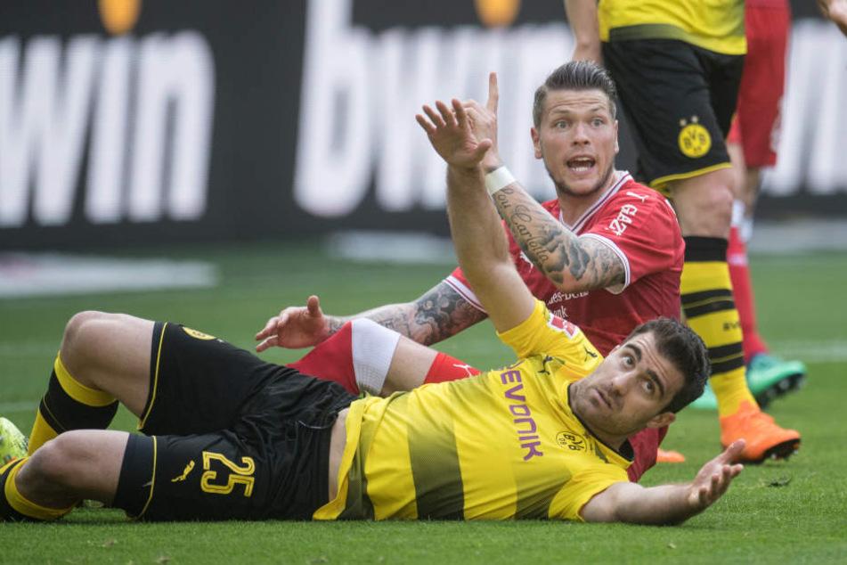 Dortmunds Sokratis (vorne) und Daniel Ginczek von Stuttgart landen nach einem Zweikampf auf dem Rasen.