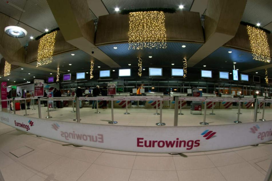 Reisende stehen am Check In Schalter der Fluggesellschaft Eurowings.