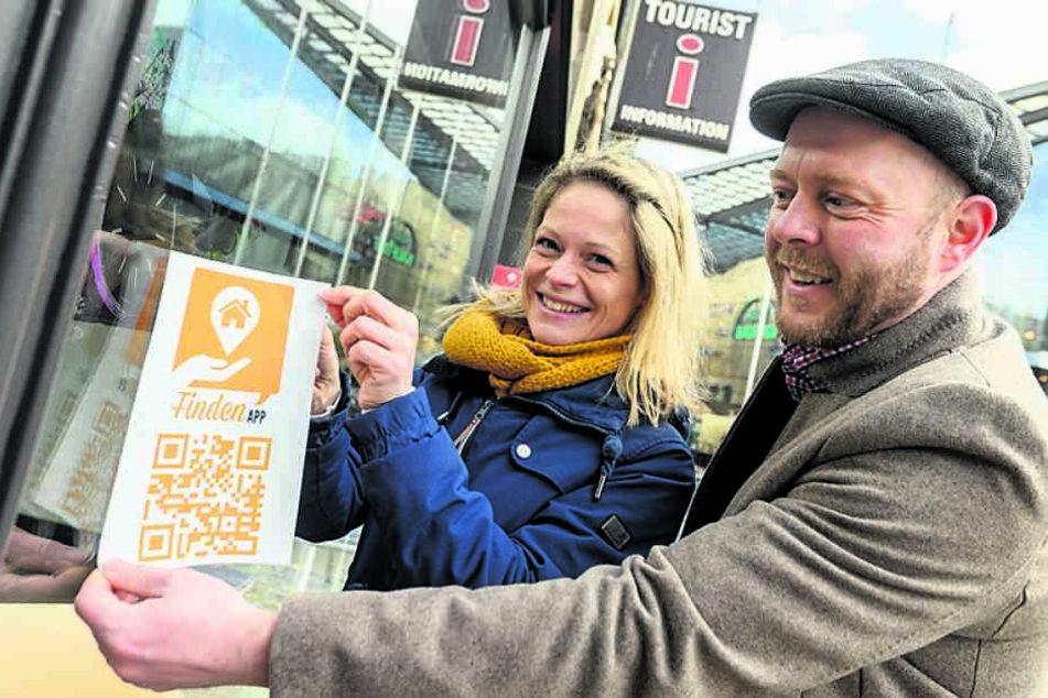 """Susan Endler (38) von der CWE und Alexander Seidel (39) vom SFZ Förderzentrum bringen ein Hinweisschild für die """"findenApp"""" an der Touristinformation an."""