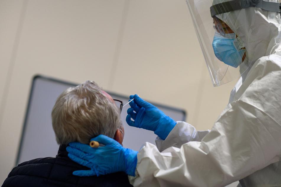 Sachsen-Anhalt, Magdeburg: Ein Mitarbeiter des Universitätsklinikums Magdeburg führt bei einem Mann einen Antigentest auf das Coronavirus durch.