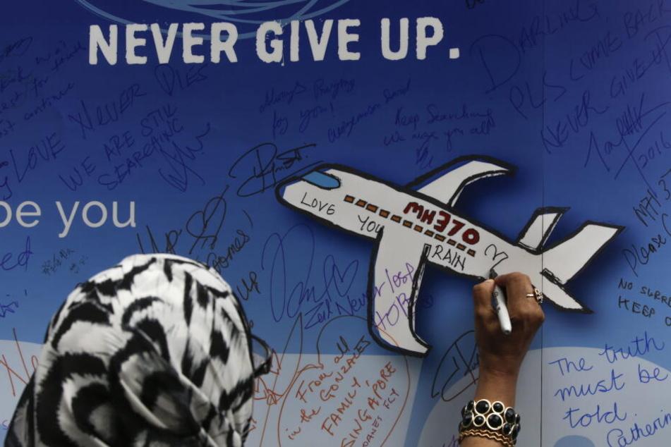 Eine Frau schreibt während einer Gedenkveranstaltung zum Flug MH370 eine Nachricht auf ein Banner.