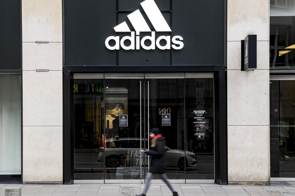 Eine Frau läuft vor dem geschlossenen Eingang eines Kaufhauses des Sportartikelherstellers adidas in der Innenstadt von Hamburg entlang.