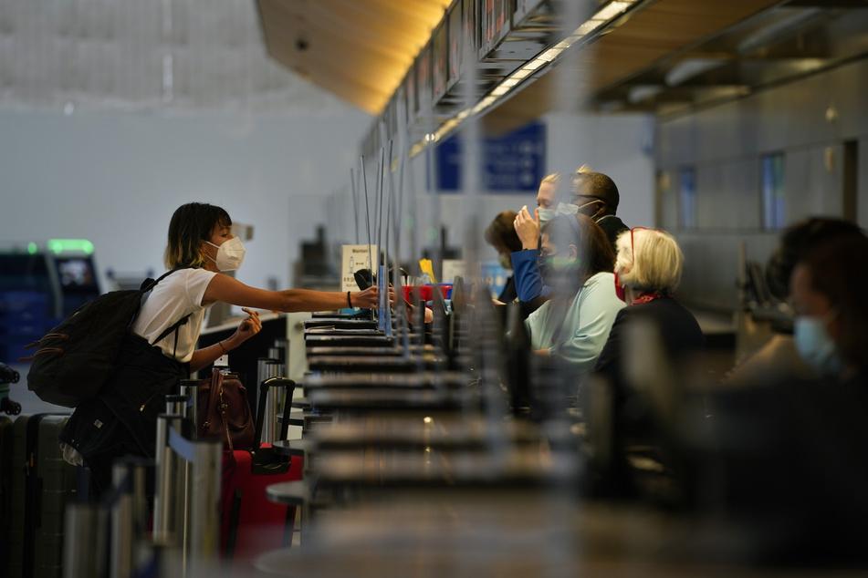 Eine Frau mit Mund-Nasen-Schutz checkt auf dem internationalen Flughafen von Los Angeles für ihren Flug ein.