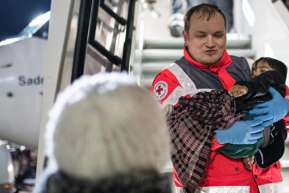 Ein kleiner schwerkranker Junge wird von Mitarbeitern des Deutschen Roten Kreuzes aus dem Flugzeug am Düsseldorfer Flughafen getragen.