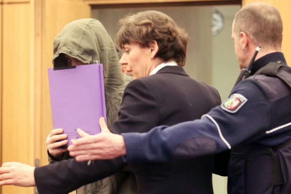Der Angeklagte (l.) wird von seiner Anwältin Susanne Tombrink und einem Justizbeamten (r.) in den Gerichtssaal geführt.