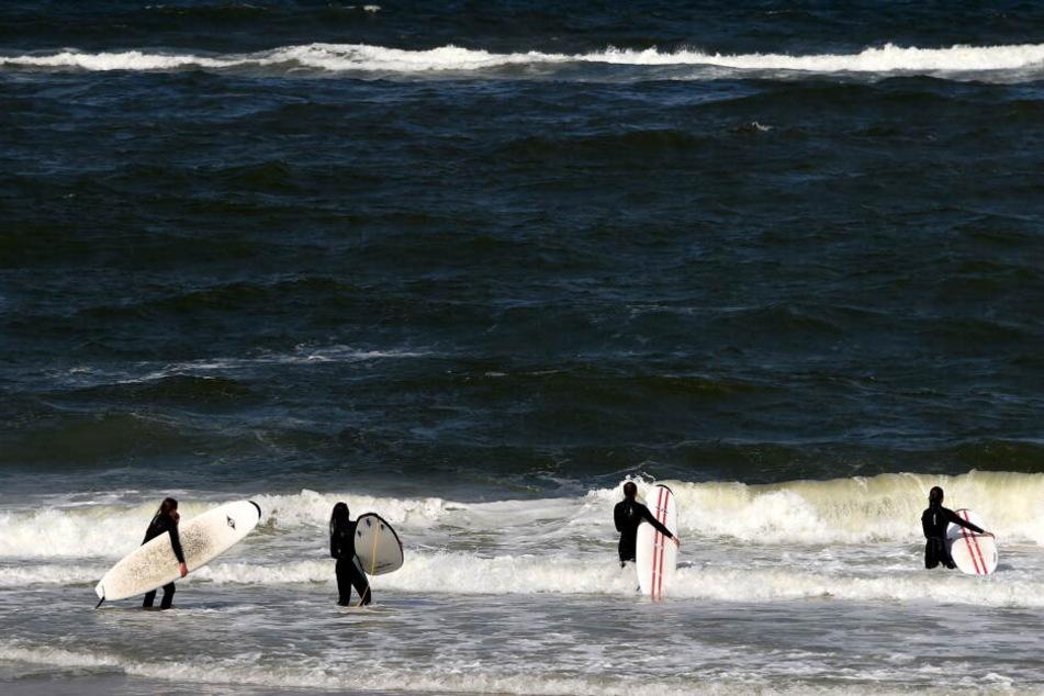 Sylt ist ein beliebter Ferienort für Surf-Fans: Hier werfen sich Teilnehmer eines Surf-Kurses am Strand von Westerland auf Sylt (Schleswig-Holstein) in die Wellen. Dank des Windes sind die Strände auf der Nordsee-Insel auch bei Kite-Surfern populär.