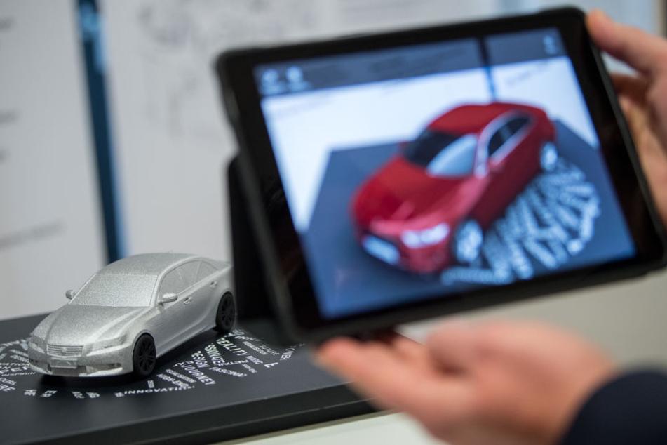 Ein Mann filmt in Stuttgart ein Automodell, um sich das Modell via augmented reality in roter Farbe anzusehen. (Archivbild)
