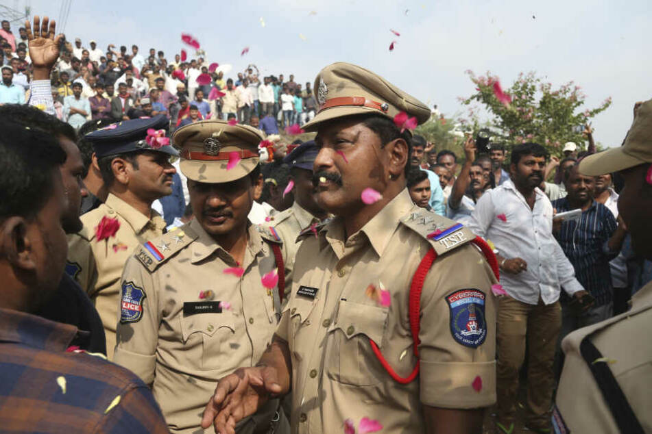 Menschen werfen Blütenblätter auf indische Polizisten.