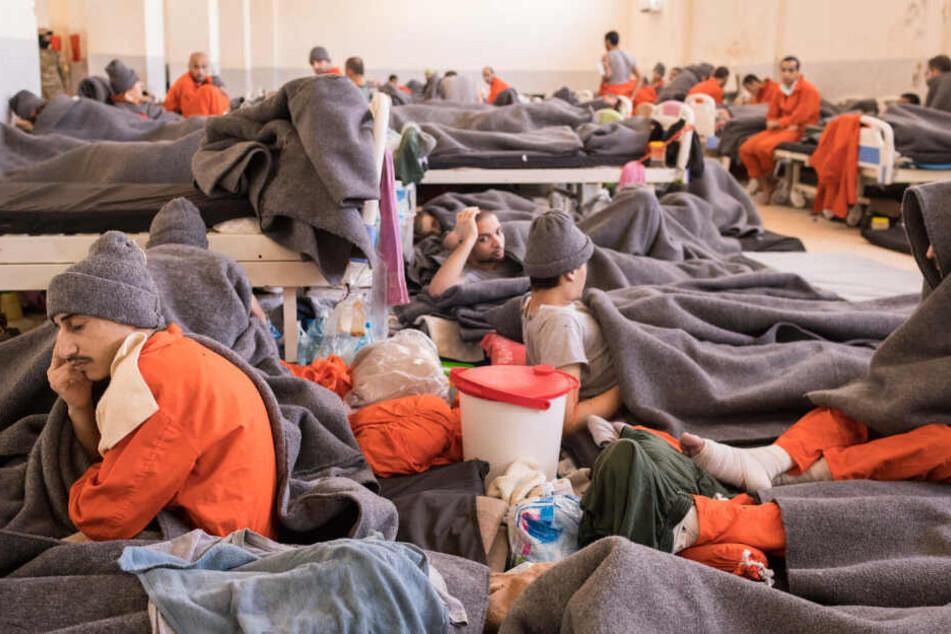Zahlreiche Männer in orangenen Overalls sitzen und liegen in einem Raum.
