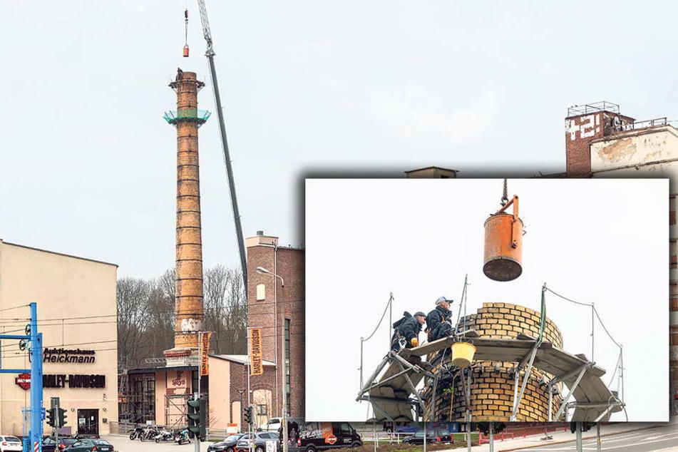 Auf dem Poelzig-Areal in der Ulmenstraße sanieren Mitarbeiter der Firma S + F  Bau den Klinkerschornstein.  Abgebrochene Ziegel sammeln sie in einer Tonne, die am Kran zu Boden schwebt.  (kl.F.).