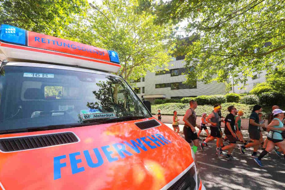 Ein Rettungswagen steht am Straßenrand der Strecke, während die Läufer passieren.