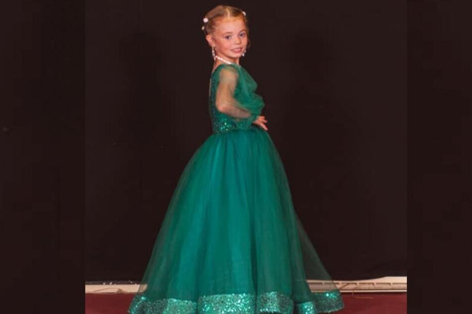 Lola (7) in einem flaschengrünen bodenlangen Ballkleid.