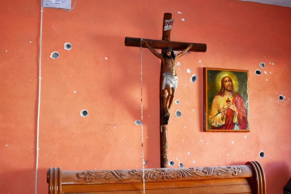 Eine Innenwand eines Hauses, an der ein Kruzifix und ein Bild mit einer Darstellung von Jesus Christus hängen, ist mit Einschusslöchern übersät.