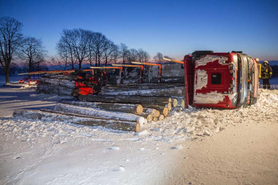 Die Holzstämme sind von dem umgekippten Laster auf das Feld gerollt.