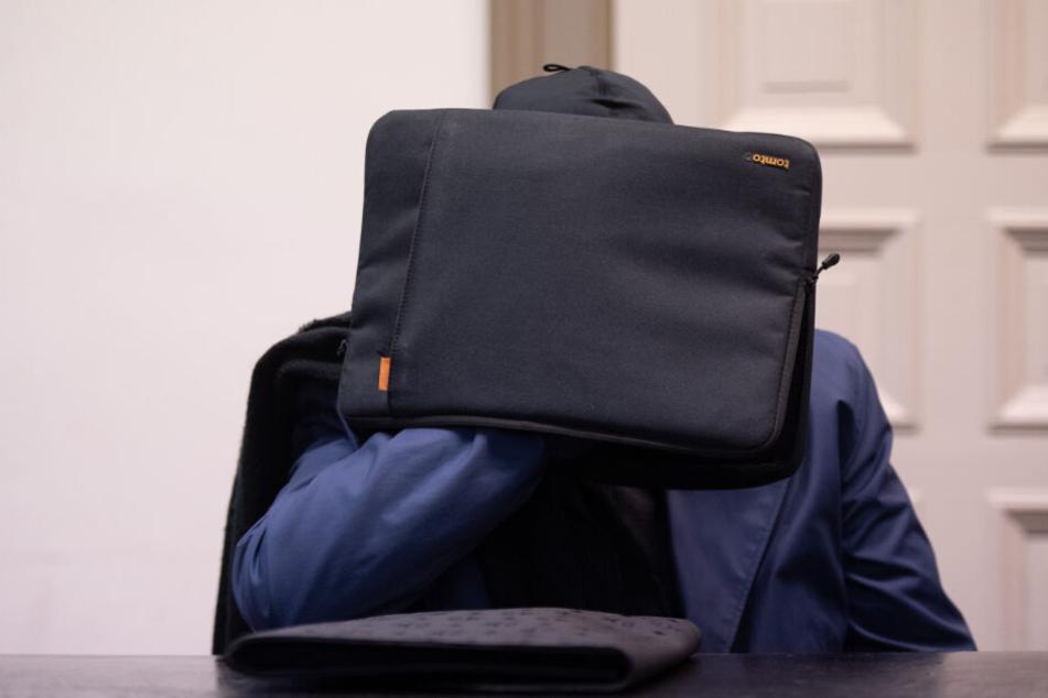 Der Angeklagte versteckt sich hinter einer Tasche.