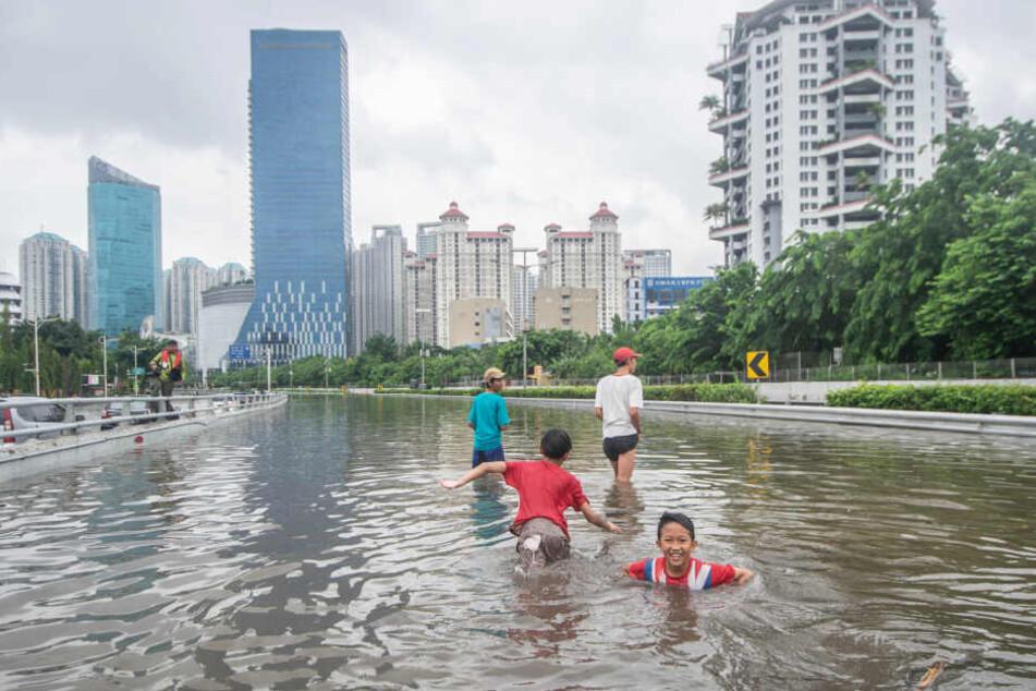Kinder spielen auf einer überfluteten Autobahn.