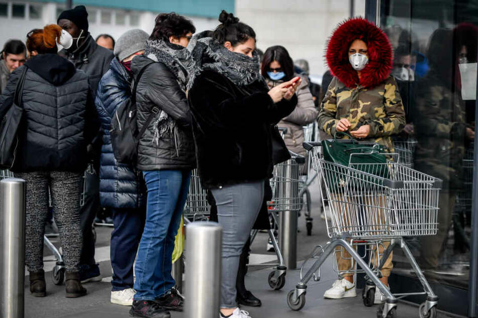 Vor einem Supermarkt stehen Kunden mit Mundschutz.