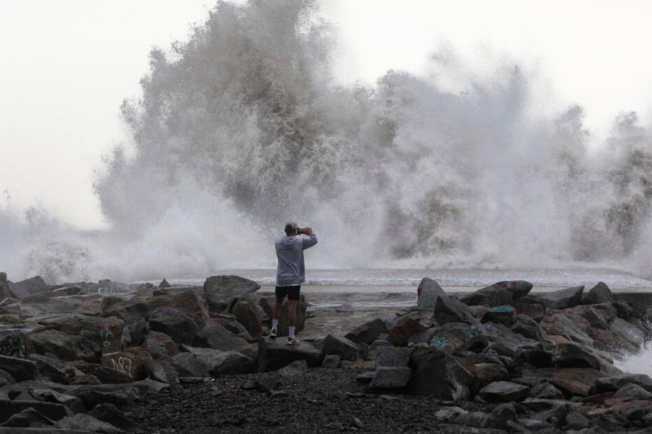 Ein Mann fotografiert durch das Wetter hervorgerufene Wasserspektakel.