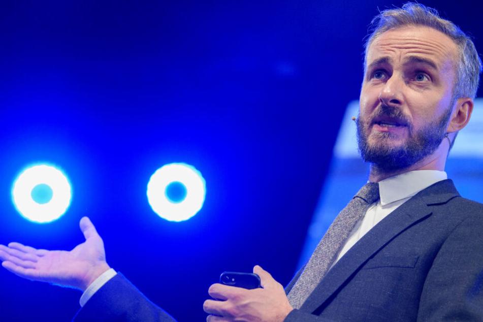 TV-Moderator und Musiker Jan Böhmermann steht auf einer Bühne im Rampenlicht.