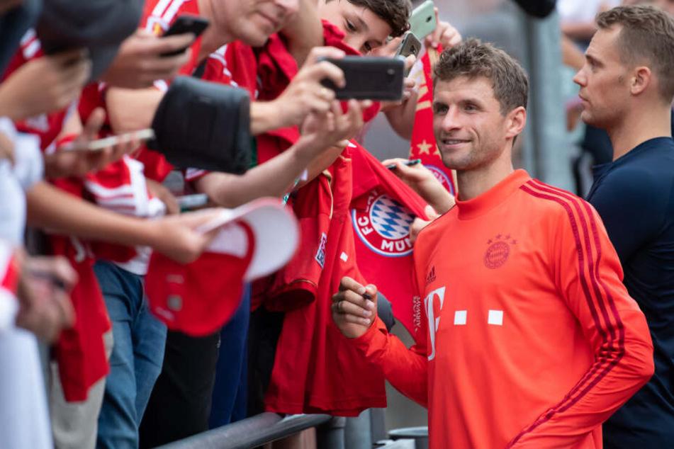 Thomas Müller (l) und Torwart Manuel Neuer schreiben nach dem Training Autogramme.