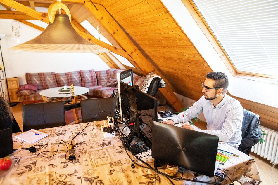 Manuel Reisdorf, 27, sitzt im Wohnzimmer seiner Freundin vor drei Monitoren, an denen er arbeitet.
