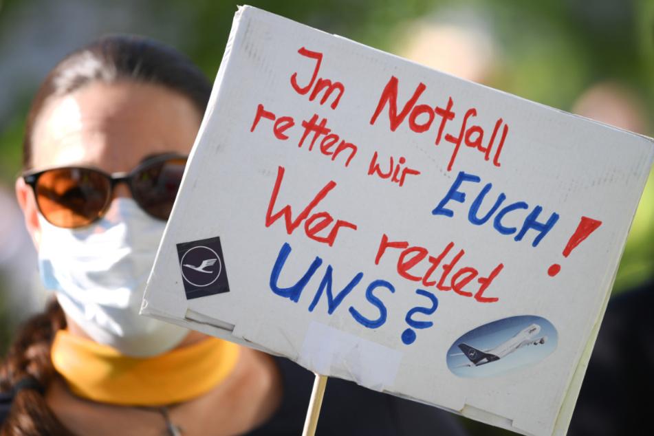 """Eine Lufthansa-Mitarbeiterin trägt während einer Demonstration vor der Lufthansa-Zentrale am Frankfurter Flughafen ein Schild mit der Aufschrift """"Im Notfall retten wir Euch ! Wer rettet uns ?""""."""