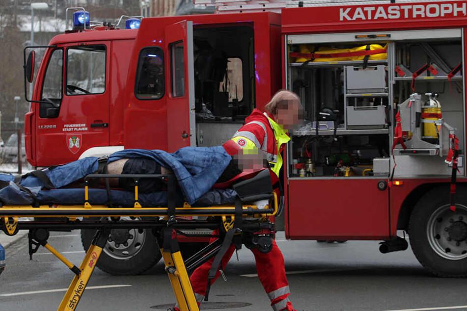 Sanitäter transportieren den schwerverletzten 23-Jährigen ab. Der Mann überlebte in der Brandwohnung.