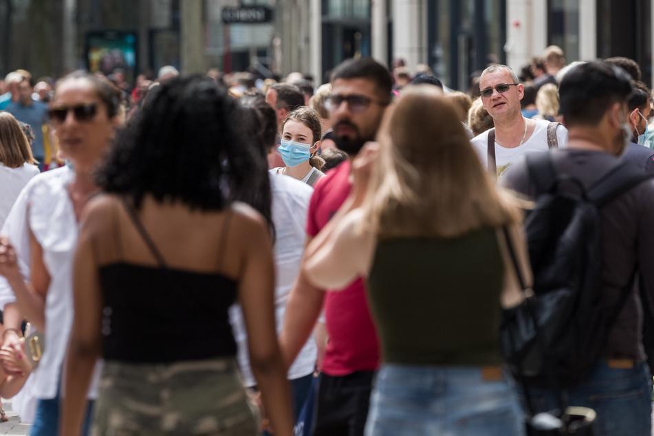 Passanten gehen bei sommerlichen Temperaturen in der Innenstadt über die Spitaler Strasse.