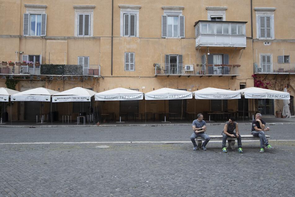Drei Männer sitzen vor einem geschlossenen Restaurant auf der Piazza Navona auf einer Bank. Durch die anhaltenden Schließungen im Rahmen der Maßnahmen zu Eindämmung der Corona-Pandemie, stehen viele Restaurants in Italien vor dem aus.