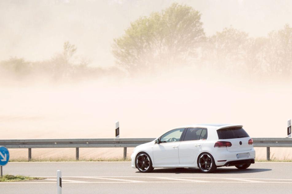 Ein Auto fährt über eine Straße in der Region Hannover, als starker Wind viel Sand von trockenen Feldern aufwirbelt.