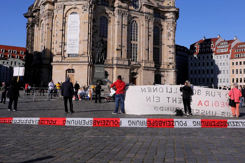 Mit Schildern und Transparenten protestieren die Pegida-Teilnehmer vor der Frauenkirche.