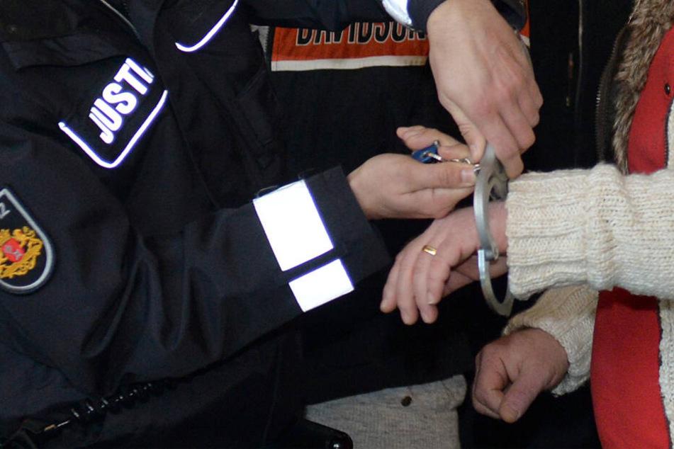 Dem Angeklagten werden vor Prozessbeginn die Handschellen abgenommen. (Archivbild)