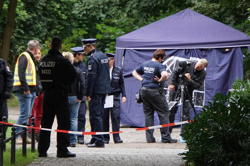 Mehrere Beamte haben den Park, in dem die Leiche des Obdachlosen gefunden wurde, nach Indizien untersucht.