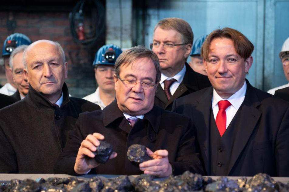 Armin Laschet (m., CDU), Ministerpräsident von Nordrhein-Westfalen, steht hinter der symbolisch letzten Lore mit Kohle.