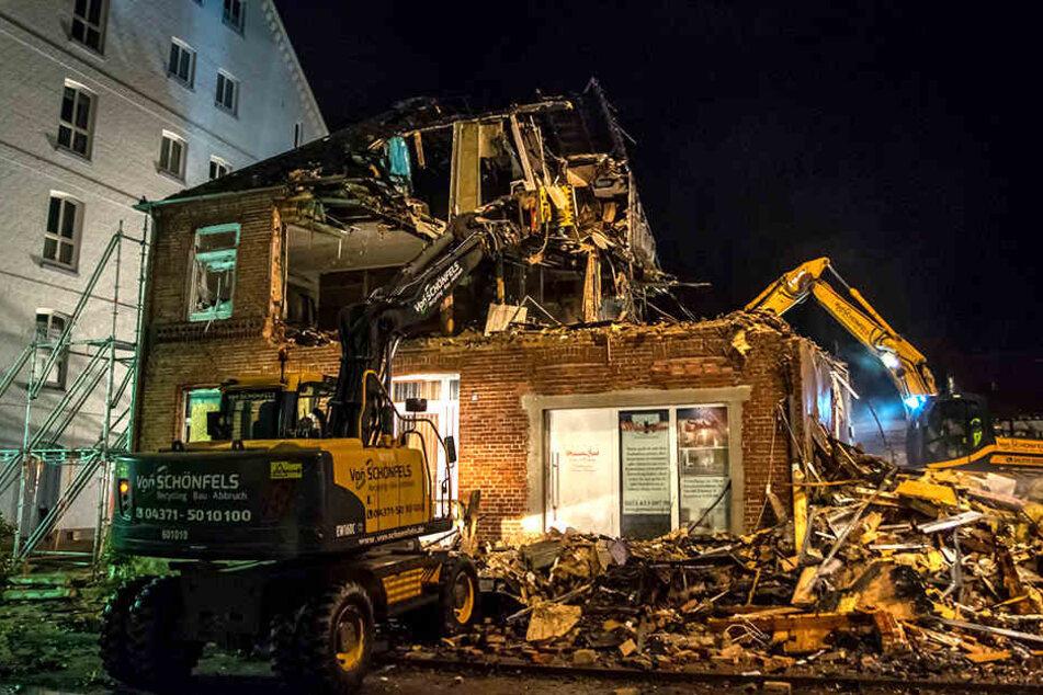 Die Bagger reißen Stück für Stück die Mauern des Gebäudes ein.
