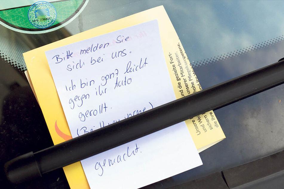 """Ein Zettel mit der Aufschrift """"Bitte melden Sie sich bei uns. Ich bin ganz leicht gegen ihr Auto gerollt"""", klemmt an einem PKW hinter einem Scheibenwischer."""