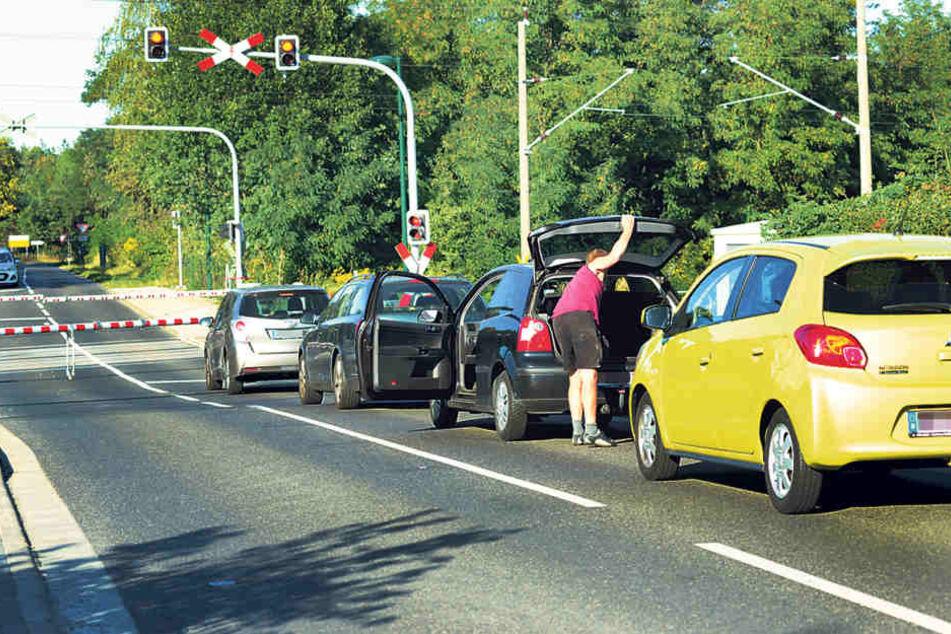 Alle Autos stehen still, wenn die Bahn passieren will.Manchmal dauert das 15  Minuten.