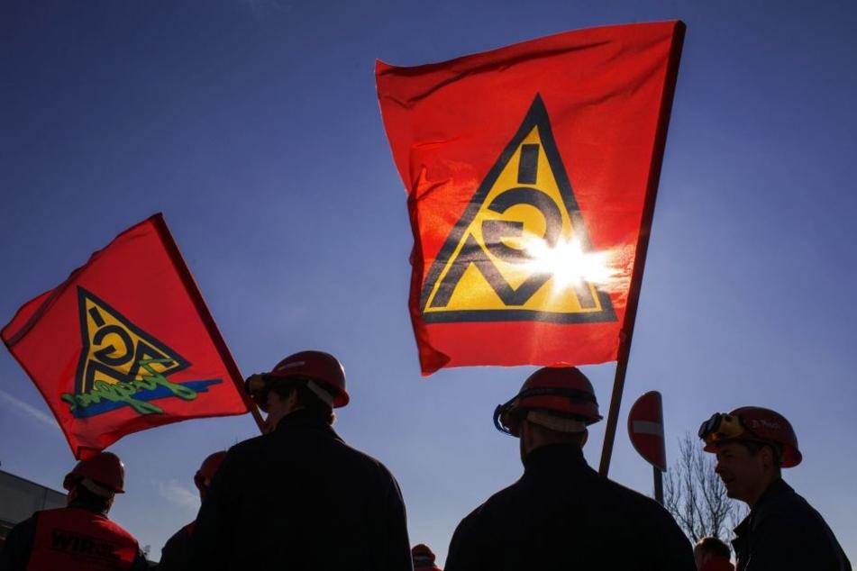 Die Fahnen der IG Metall wehen im Wind. Die Gewerkschaft schwört die Beschäftigten der sächsischen Metall- und Elektroindustrie bei den Warnstreiks am Montag auf einen harten Arbeitskampf ein.