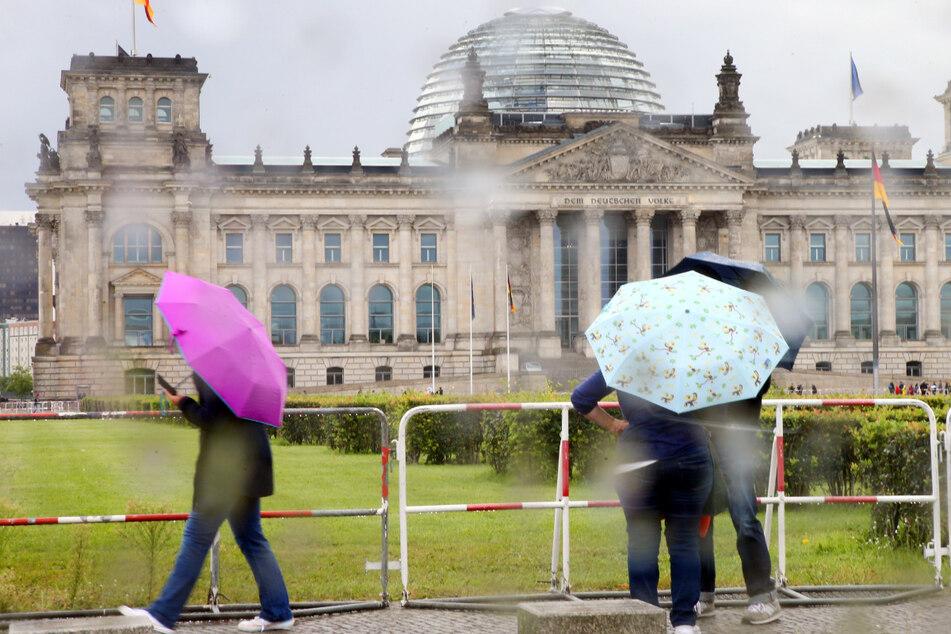 Passanten trotzen dem Regen und spazieren durch das Regierungsviertel. Am Donnerstag müssen Berliner mit typischen Herbstwetter rechnen.