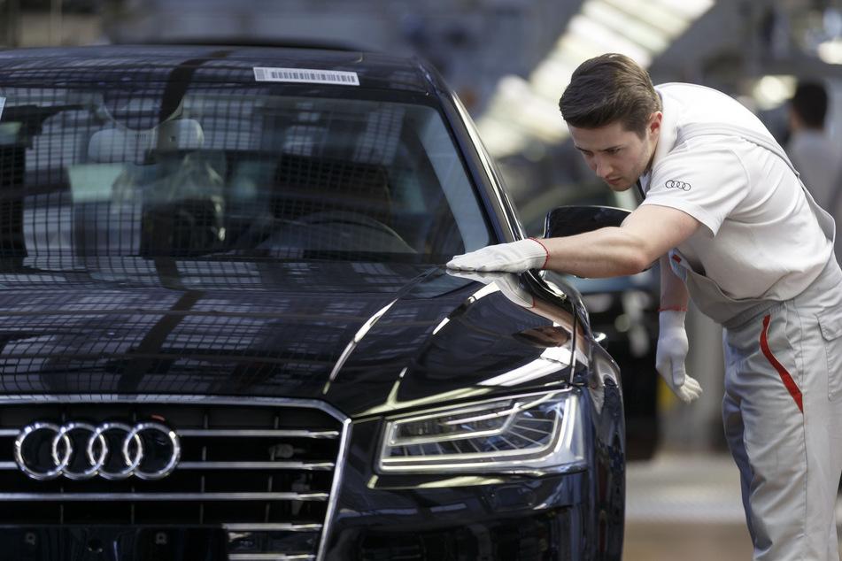 Ein Werksmitarbeiter kontrolliert in einer Produktionshalle von Audi an einem Bandende einen A8. Das Unternehmen nutzt nun gendergerechte Sprache.