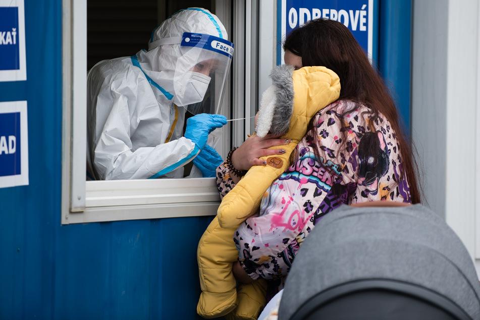 Ein Mitarbeiter des Gesundheitswesens in Schutzkleidung nimmt während der Corona-Massentests eine Nasenabstrichprobe von einem Kleinkind in Bratislava.