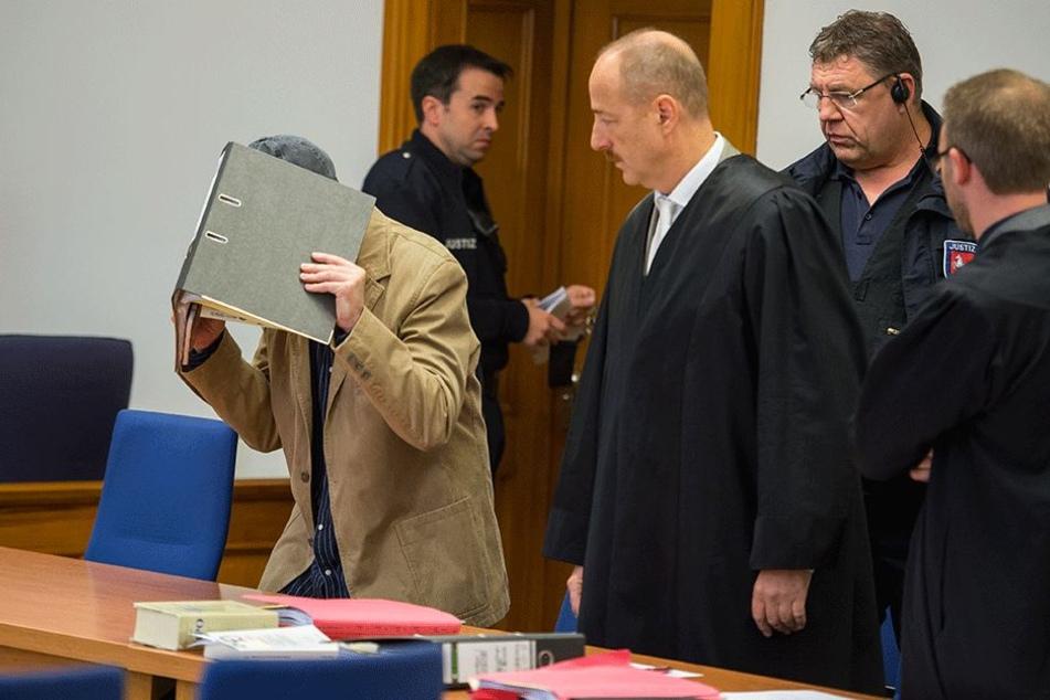 Der Angeklagte (l.) betritt am 28. September in Lüneburg bei Prozessbeginn den Gerichtssaal. Der 42-jährige Zeitungsausträger muss sich wegen Mordes vor dem Landgericht Lüneburg verantworten.