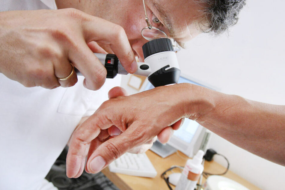 Ein Hautarzt untersucht in seiner Praxis mit einem Vergrößerungsglas die Haut einer Patientin bei einer Hautkrebs-Früherkennung.