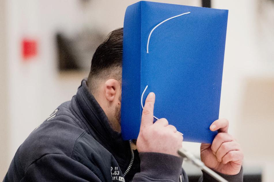 Niels Högel verdeckt im Gerichtssaal sein Gesicht. Er ist wegen 100-fachen Mordes angeklagt.