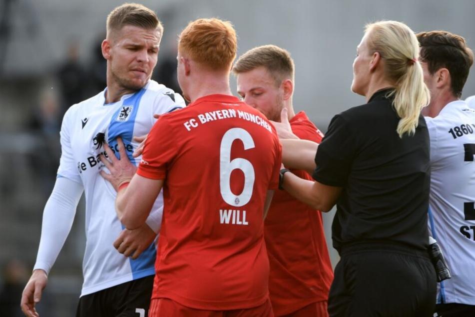 Hitzige Derby-Atmosphäre: TSV-Sechser Daniel Wein (l.) wird von den FCB-Spielern Paul Will (Zweiter von links) und Leon Dajaku bedrängt, Schiedsrichterin Bibiana Steinhaus geht dazwischen.