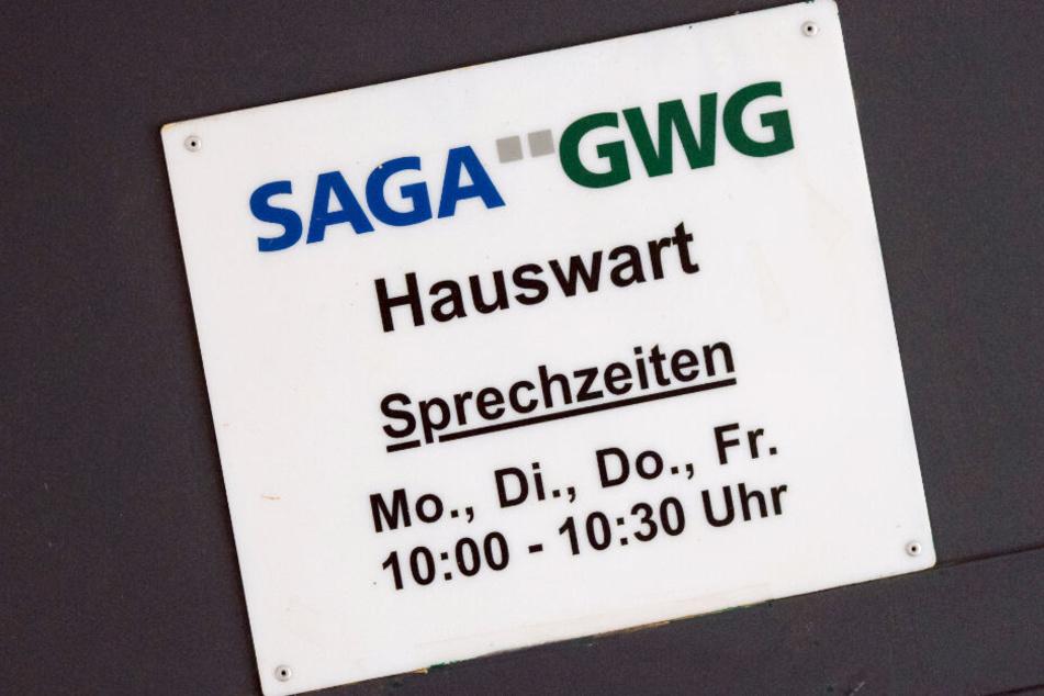 """Ein Schild """"SAGA GWG Hauswart"""" hängt in Hamburg an einem Mehrfamilienhaus des Immobilienunternehmens."""