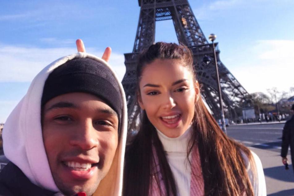 Das verliebte Paar posiert vor dem Pariser Eifelturm.
